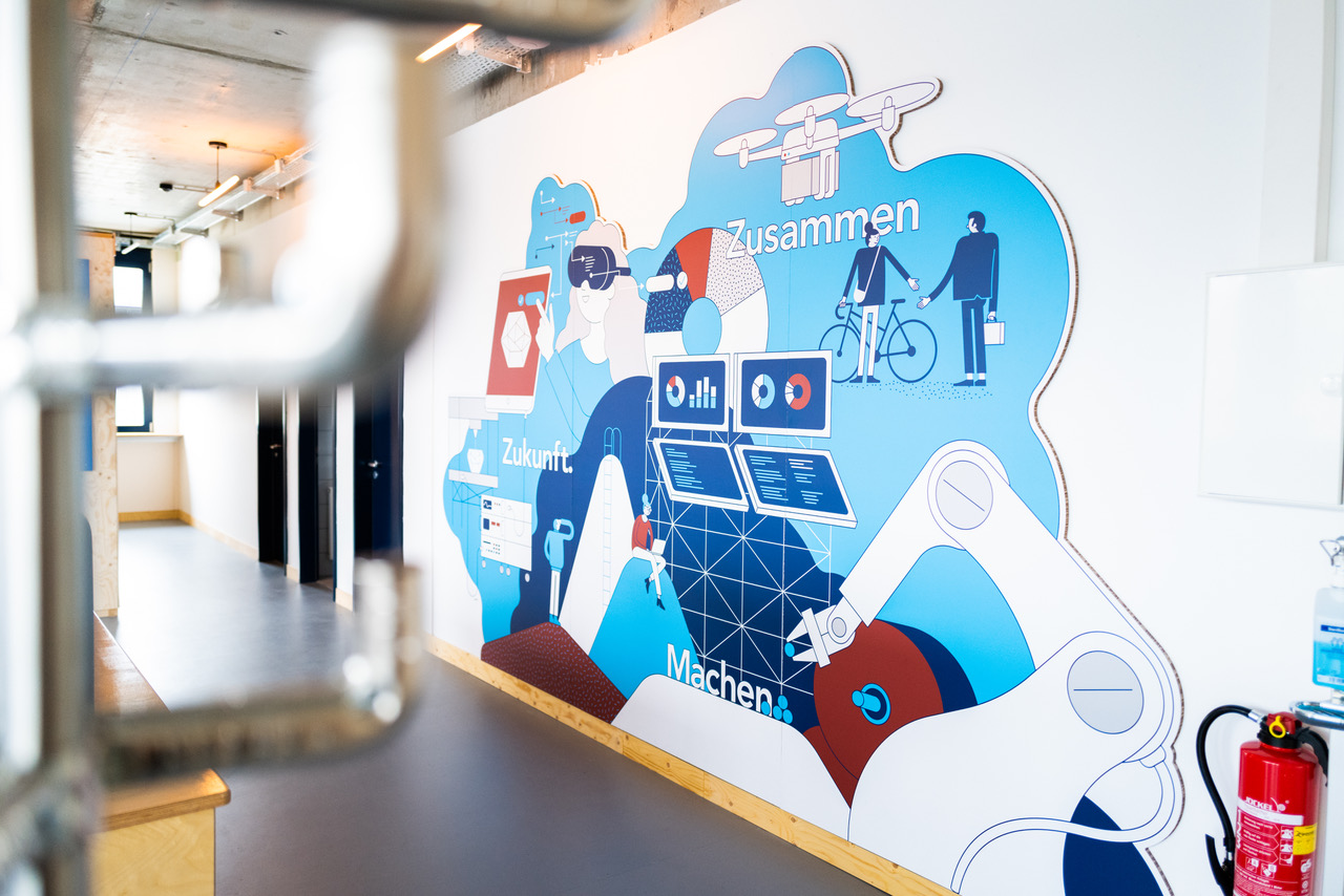 Cafe area area at INNOPORT Reutlingen with wall graphic by Axel Pfaender. Photo by Melanie Schneider